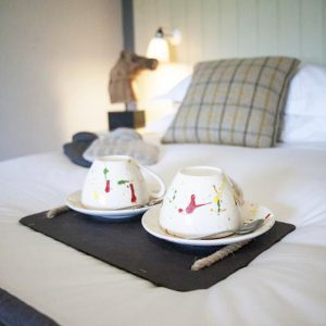 A closeup of fun colourful teacups places on the bed