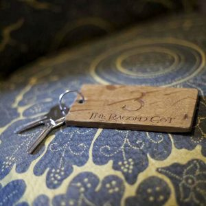 A key to a Ragged Cot bedroom on a blue decorative fabric