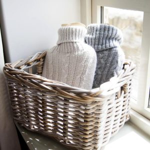 White and grey hot water bottles displayed in a basket